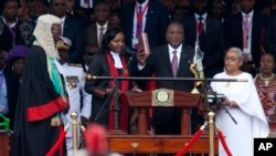 Kenyan President Uhuru Kenyatta, center, is sworn in as his wife, Margaret, right, looks on during his inauguration at Kasarani Stadium in Nairobi, Kenya, Nov. 28, 2017.