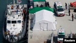 Sebuah ambulans membawa jenazah penumpang kapal tenggelam di pelabuhan Jindo, Korea Selatan (23/4). (Reuters/Issei Kato)
