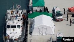 """Sebuah mobil ambulance pembawa jenasah seorang penumpang kapal feri """"Sewol"""" yang tenggelam di lepas pantai Jindo, bergerak meninggalkan pelabuhan Jindo, tempat para anggota keluarga korban berkumpul (23/4)."""