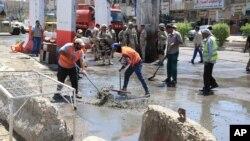 Para pekerja membersihkan puing-puing pasca serangan bom di distrik Shaab, di Baghdad, Irak akhir bulan lalu (30/5).
