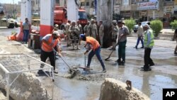 FILE - Municipality workers clean up debris in the aftermath of a bomb attack in Baghdad northern Shaab district, Iraq, May 30, 2016.
