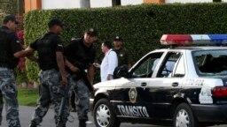 Agentes de la policía junto a una patrulla, en la que dos agentes de tránsito fueron abatidos a tiros, en Navolato, a unos 25 km al oeste de Culiacán en el estado mexicano de Sinaloa. [Foto de archivo]