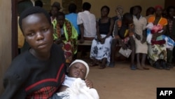 Women wait with their babies to be tested for HIV at a hospital in Bududa, eastern Uganda, September 27, 2011.
