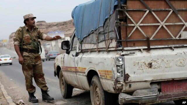 A Yemeni soldier stops a car at a checkpoint in a street leading to the U.S. embassy in Sanaa, Yemen, Aug. 4, 2013.