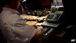 FILE - A man uses a cash register at a market in Madrid, Spain.