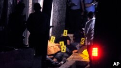 FILE - Police investigators stand over the bodies of six men who were killed in Tegucigalpa, Honduras, Sept. 14, 2016.