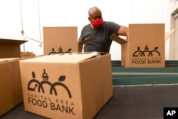 A volunteer pack boxes of food for distribution, at The Capital Area Food Bank, in Washington, Oct. 5, 2021.