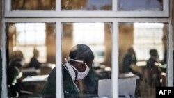 Siswa kelas 7 SMP Sitoromo di Sterkspruit, Afrika Selatan, duduk di kelasnya sambil mengenakan masker, 6 Juli 2020.