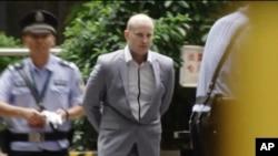 Warga Selandia Baru, Peter Gardner, tengah, dikawal oleh polisi di Pengadilan kota Guangzhou atas tuduhan penyelundupan obat-obatan terlarang, Kamis 7 Mei 2015. (AP Photo/APTN)