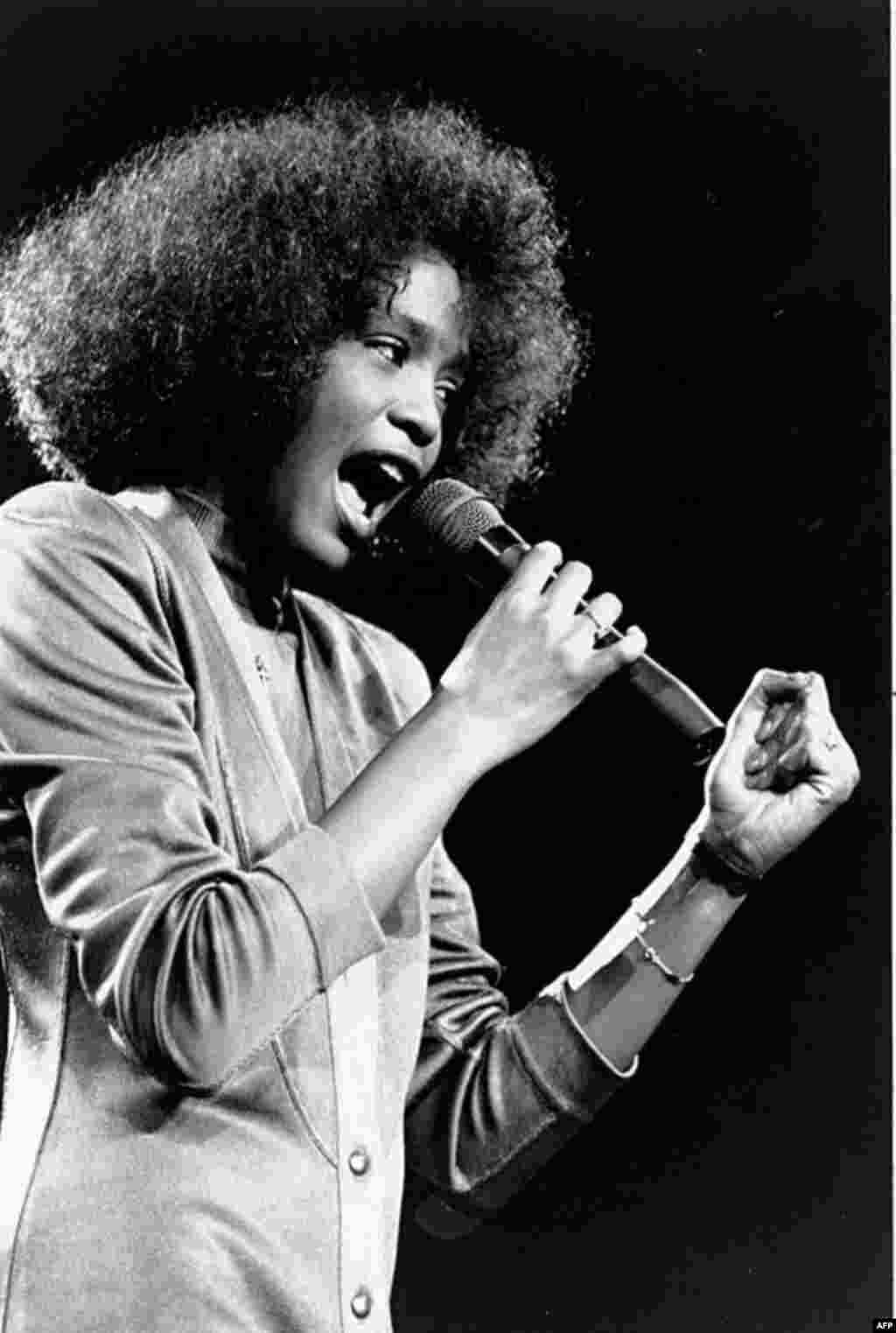 In this May 10, 1986 photo, American singer Whitney Houston sings during a benefit concert at Boston Garden. Houston died February 11, 2012, at age 48. (AP)