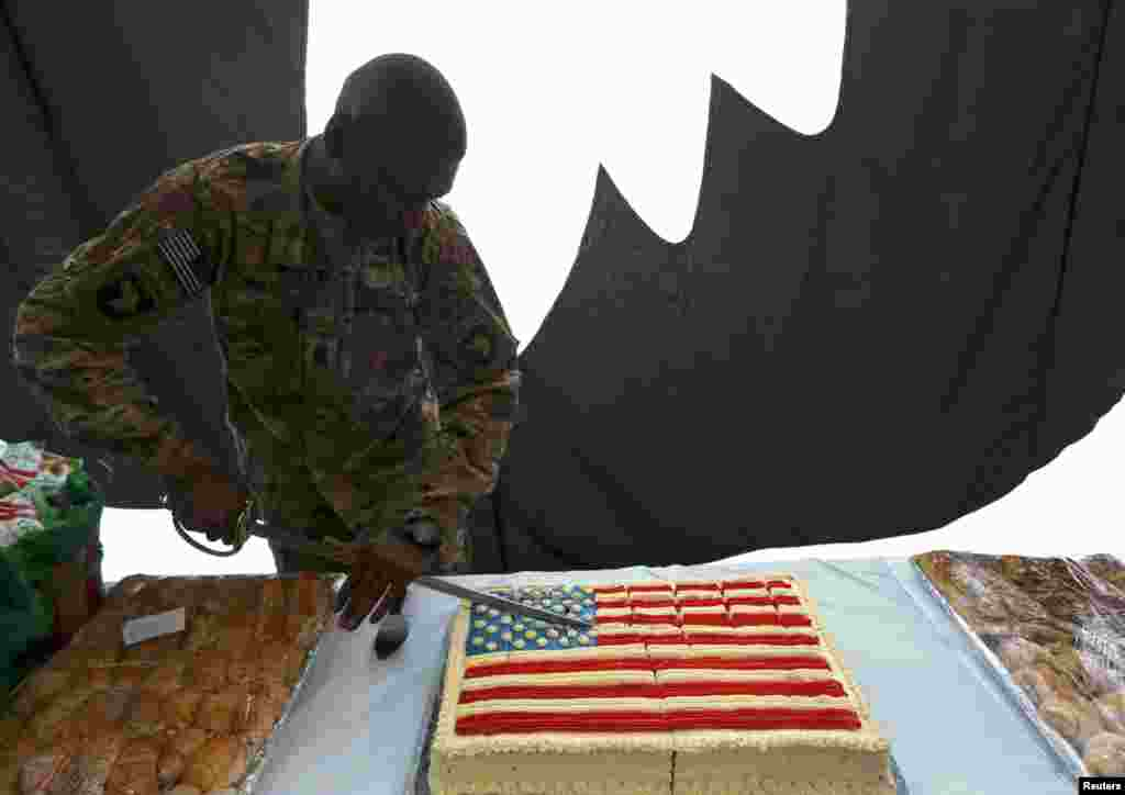 A U.S. soldier cuts into a cake during Fourth of July celebrations at the Bagram airbase, north of Kabul, Afghanistan, July 4, 2013.