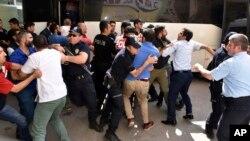 터키 에르주룸 시민들이 지난 19일 쿠데타 배후 의심을 받고있는 판사를 공격하고 있는 가운데, 경찰이 제지하고 있다.