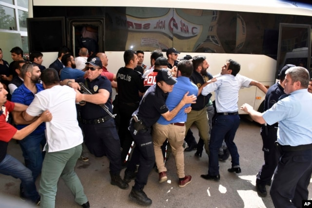 Police officers try to stop people attacking a judge believed to be member of a coup plotter group in Erzurum, Turkey, July 19, 2016.