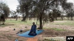 Un pasteur peul fait sa prière du soir avant de partir pour trouver un camp pour la nuit à Barkedji le 20 juillet 2020, ils sont sur la route depuis deux semaines, en direction du nord vers la frontière mauritanienne.