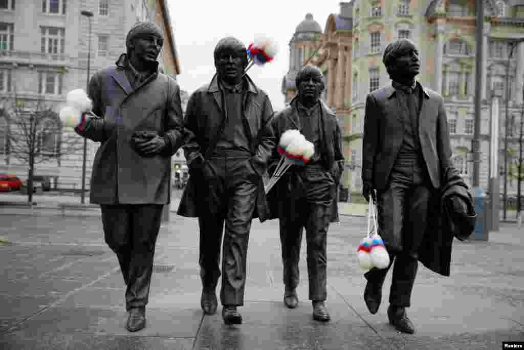 "A statue of The Beatles sports ""tickling sticks"", comedian Ken Dodd's quintessential prop, ahead of Dodd's funeral in his home town of Liverpool, Britain."