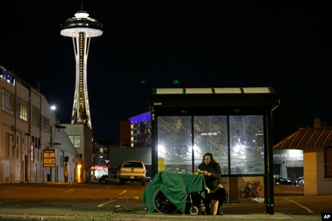Dave Chung, who says he has been homeless for five years on the streets of California and Washington state, eats a meal before bedding down in a bus shelter in view of the Space Needle in Seattle, Oct. 30, 2017.