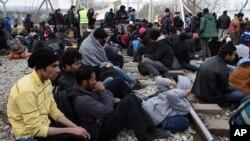 Des réfugiés afghans sont assis sur le chemin de fer qui relie la Grèce avec la Macédoine, 22 février 2016.
