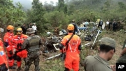 In this photo released by the Guatemalam Volunteer Fire Department, firefighters and soldiers inspect the scene of a helicopter crash in Huehuetenango, Guatemala, near the border with Mexico.