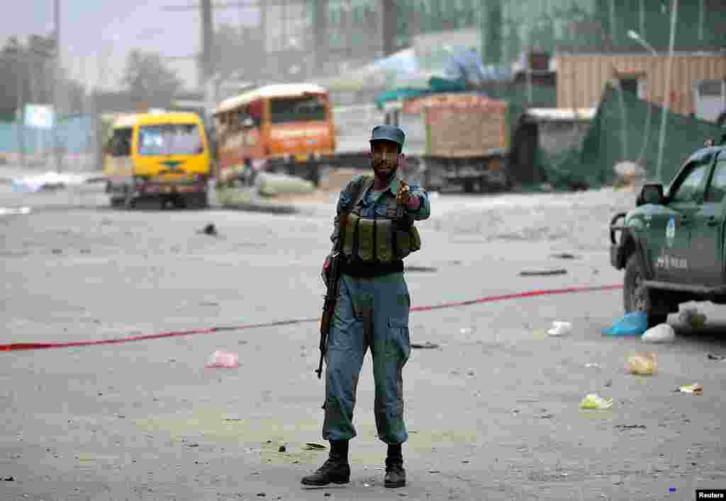 An Afghan police officer keeps watch at the site of bomb blasts in Kabul, June 6, 2014.