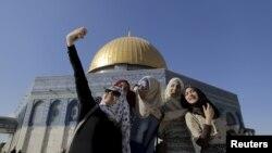 Warga Palestina Sanaa Abu Jaudi (kiri), 16, dari kota Jenin di Tepi Barat, mengambil swafoto di depan Kubah Batu di Yerusalem bersama kawan-kawannya (29/6). (Reuters/Ammar Awad)