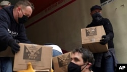 Volunteers unload boxes of food from a truck for a distribution program run through Mosaic West Queens Church in the Sunnyside neighborhood of the Queens borough of New York on Monday, Feb. 22, 2021. (AP Photo/Emily Leshner)