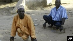 Polio sufferers Yusuf Umar, right, and Aminu Ahmed use wooden blocks to propel themselves through the dusty streets of Kano, Nigeria, November 28, 2008.