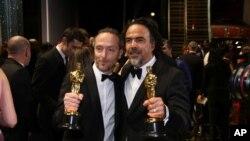 """Emmanuel Lubezki, ganador del premio a la mejor fotografía por """"The Revenant"""", a la izquierda, y Alejandro G. Inarritu, ganador del premio al mejor director de """"The Revenant"""", aparecen detrás del escenario en los Oscar el domingo, 28 de febrero de 2016."""