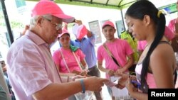 Soledad's Mayor Joao Herrera (L) gives a woman, condoms and kits with insect repellent during a campaign to fight the spread of Zika virus in Soledad municipality near Barranquilla, Colombia, in this Feb. 1, 2016 handout photo supplied by the Soledad Mun