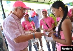 Soledad's Mayor Joao Herrera (L) gives a woman, condoms and kits with insect repellent during a campaign to fight the spread of Zika virus in Soledad municipality near Barranquilla, Colombia, in this Feb. 1, 2016 handout photo supplied by the Soledad Municipality.