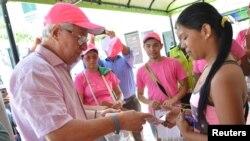 Walikota Soledad Joao Herrera (kiri) memberikan paket kesehatan dalam kampanye mengatasi penyebaran virus Zika di Soledad dekat Barranquilla, Kolombia, 1 Februari 2016.