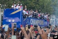 Para penggemar sepak bola menyambut timnas Perancis yang berparade menggunakan bus terbuka di sepanjang Champs-Elysees di Paris, Perancis, setelah menang atas Kroasia pada laga final Piala Dunia 2018, 16 Juli 2018.