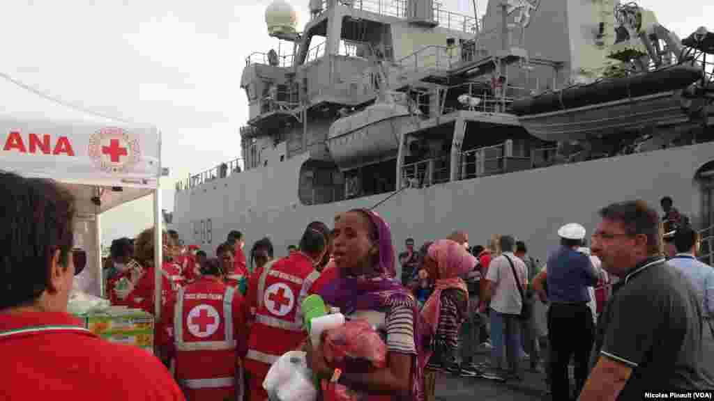 Maaikatan kungiyar agaji ta Red Cross suna kula da bakin haure a Catania, Sicily