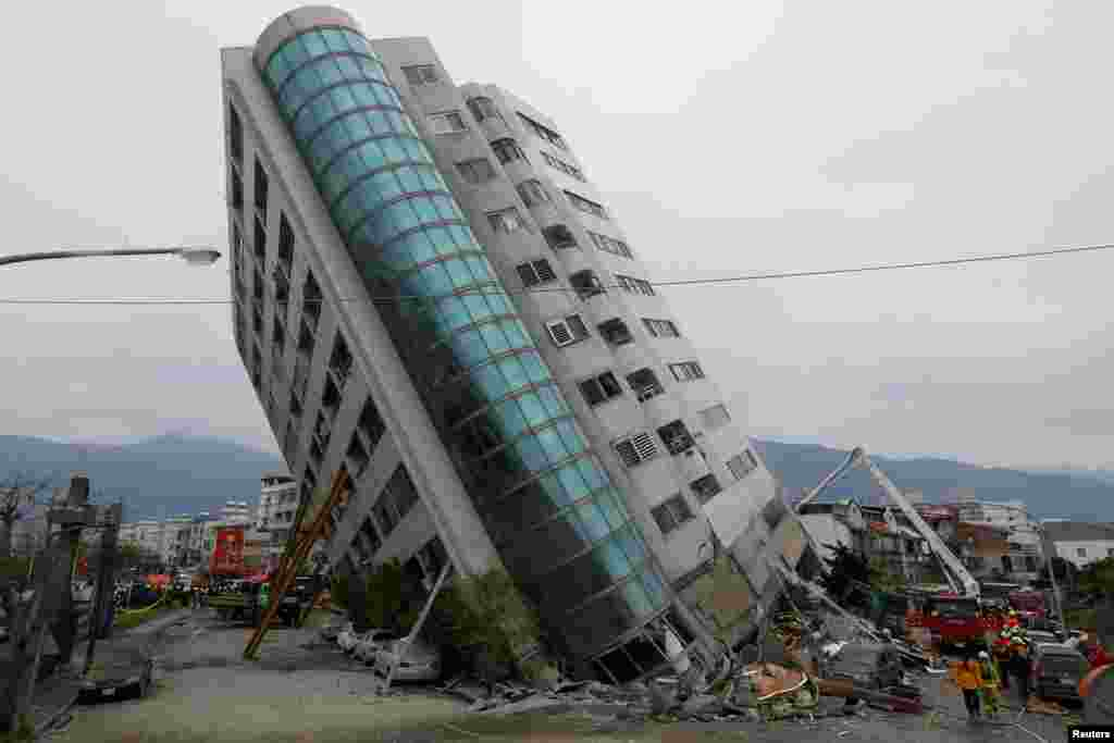 Rescue workers are seen by a damaged building after an earthquake hit Hualien, Taiwan.