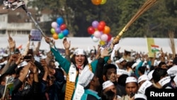 A supporter of Aam Aadmi (Common Man) Party (AAP) cheers after its leader Arvind Kejriwal took an oath as the new chief minister of Delhi during a swearing-in ceremony at Ramlila ground in New Delhi, Dec. 28, 2013.