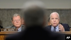 Senаtor John McCain (R) asks a question of defense secretary nominee Chuck Hagel (C) on Capitol Hill in Washington January 31, 2013, as Senator James Inhofe (L) looks on.