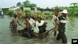 Une famille transportée dans un chariot en pleine inondation à Kinshasa, 31 mars 1997.