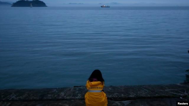 Một người có thân nhân mất tích khi chiếc phà Sewol bị chìm, ngồi ở hải cảng Jindo, nhìn về hướng tai nạn xảy ra, 18/4/14