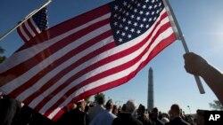Anggota Marinir AS Terri Shreiner mengibarkan bendera AS dalam pawai di Washington Memorial, menuntut penghentian penutupan sebagian kegiatan pemerintah, di Washington, 15 Oktober 2013.