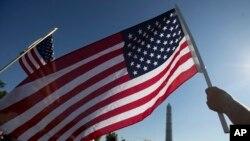 資料照:一人在華盛頓紀念碑附近揮舞美國國旗