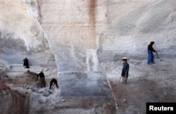 FILE - Men work at Taqcha Khana salt mine in Namak Aab district of Takhar province northeast of Kabul, March 10, 2009.