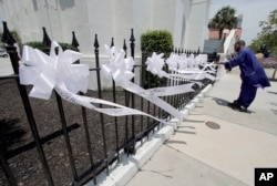 FILE - A man takes video of nine ribbons placed in front of the Mother Emanuel AME Church in Charleston, S.C., June 17, 2016, on the anniversary of the shooting deaths of nine black parishioners during a Bible study at the church.