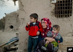FILE - Members of a Syrian Kurdish refugee family from Kobani sit in the village of Alanyurt on the Turkish side of the Turkey-Syria border.