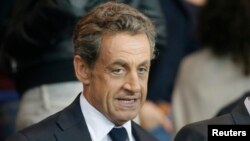 Former French president Nicolas Sarkozy attends a soccer match after a prime-time news interview at the Parc des Princes Stadium, Sept. 21, 2014.
