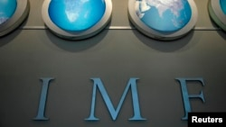 FILE - The IMF nameplate is displayed on a wall at the headquarters during the World Bank/International Monetary Fund Spring Meetings in Washington.