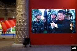 FILE - A man rests next a video screen showing Chinese President Xi Jinping holding a rifle at an exhibition highlighting China's achievements under five years of his leadership at the Beijing Exhibition Hall in the capital city, Oct. 23, 2017.