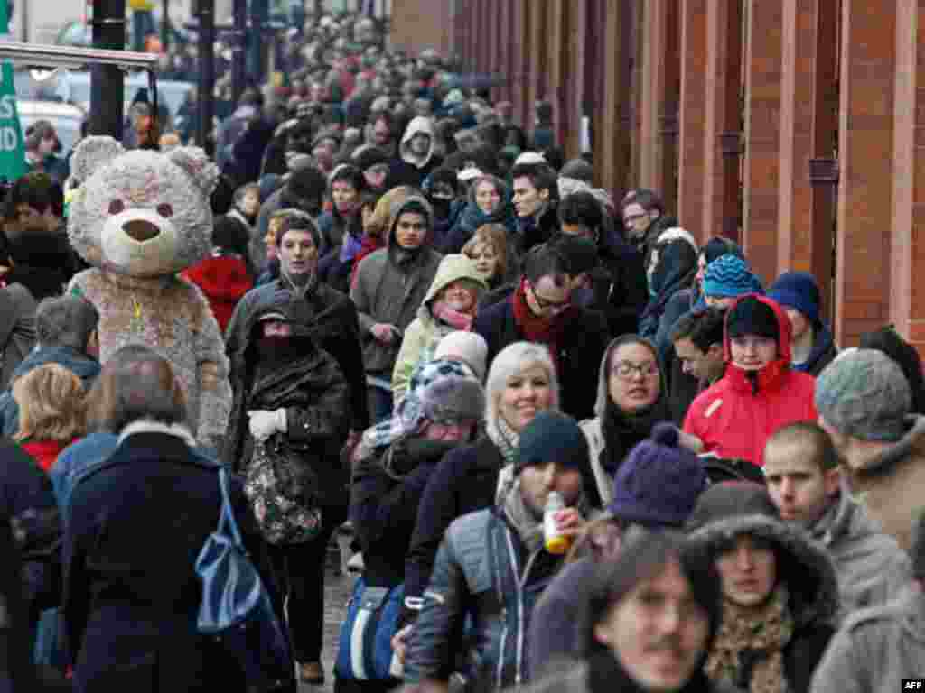 A performer dressed as a bear entertains Eurostar passengers queueing for trains at St Pancras station, in London December 21, 2010. Snow and freezing temperatures grounded flights and disrupted road and rail links across northern Europe on Monday, strand