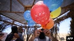 Pendukung Palestina terlihat menyiapkan balon yang mudah menyulut api dalam sebuah aksi protes terhadap militer Israel yang dilakukan di perbatasan Gaza pada 15 Juni 2021. (Foto: AFP/Mahmud Hams)