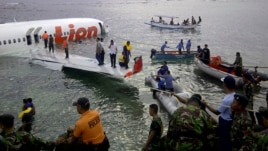 This photo released by Indonesia's National Rescue Team shows rescuers at the crash site of a Lion Air plane in Bali, Indonesia, Apr. 13, 2013.