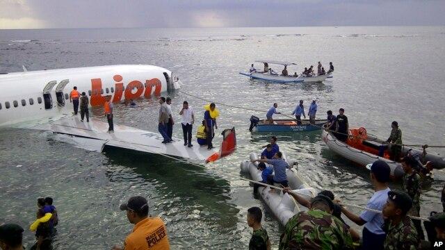 Cảnh cảnh sát và nhân viên cứu hộ dùng xuồng cứu sinh sơ tán hành khách trên chiếc máy bay Boeing 737, do hãng hàng không giá rẻ Lion Air điều hành, ngày 13/4/2013.