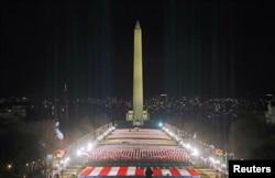 """Lampu sorot menerangi """"bendera"""" di National Mall, yang menjadi simbol kehadiran warga AS untuk menghormati pelantikan Presiden terpilih AS Joe Biden di Washington, AS, 18 Januari 2021. (REUTERS / Jim Bourg)"""